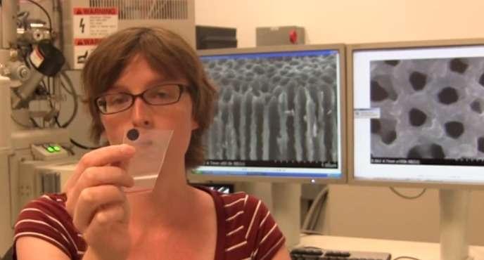 Eleanor Gillette, l'une des chercheuses du NanoCenter de l'université du Maryland, montre le prototype de batterie dont la taille n'excède pas celle d'un timbre-poste. Il s'agit d'une feuille de céramique percée de plusieurs millions de nanopores. À l'arrière-plan, sur les deux écrans d'ordinateur, on peut voir l'aspect de cette structure. © University of Maryland NanoCenter