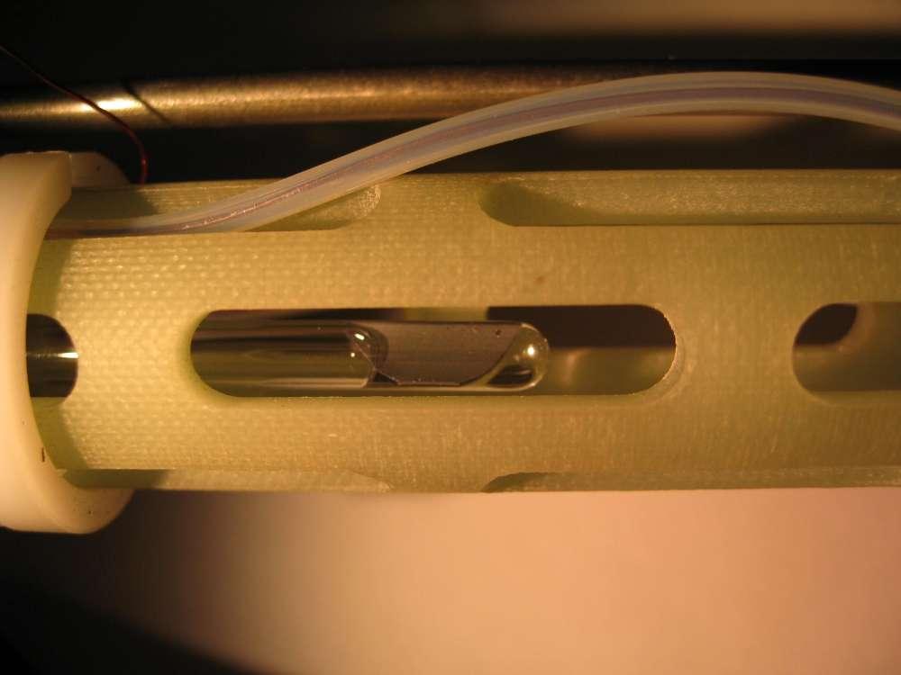 L'atome de phosphore est enfermé dans un bloc de silicium (la masse grise) et ainsi protégé des influences extérieures, permettant de conserver l'information quantique plus d'une seconde. Le bloc est placé dans un tube en verre, lui-même installé au cœur d'un résonateur faisant varier le champ magnétique. © Stephen Lyon/Princeton University