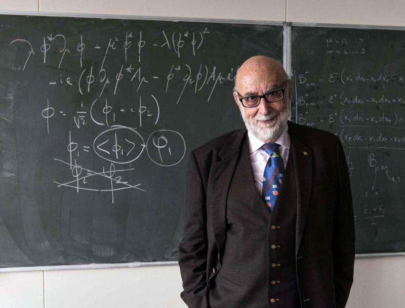 Derrière le prix Nobel de physique 2013 François Englert, un tableau porte les équations du mécanisme de Brout-Englert-Higgs responsable de l'existence de la masse des bosons de jauge du modèle standard. On pense que le champ associé au boson de Higgs est aussi responsable de la masse des particules de matière comme les quarks et les électrons. © Maximilien Brice, Cern