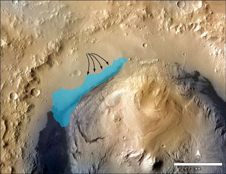 La reconstitution hypothétique du lac qui, un jour, a sans doute empli une petite partie du cratère Gale. La barre d'échelle indique une distance de 25 km, et les flèches montrent les écoulements qui ont alimenté cette réserve d'eau douce et de pH neutre. Ce lac a dû exister il y a environ trois milliards d'années, mais on ne sait pas quand avec précision, ni combien de siècles ou de millénaires il a subsisté. La cartographie du cratère, qui a permis d'estimer l'extension du lac, a été réalisée grâce aux données de MRO (Mars Reconnaissance Orbiter). © Nasa, JPL-Caltech, MSSS