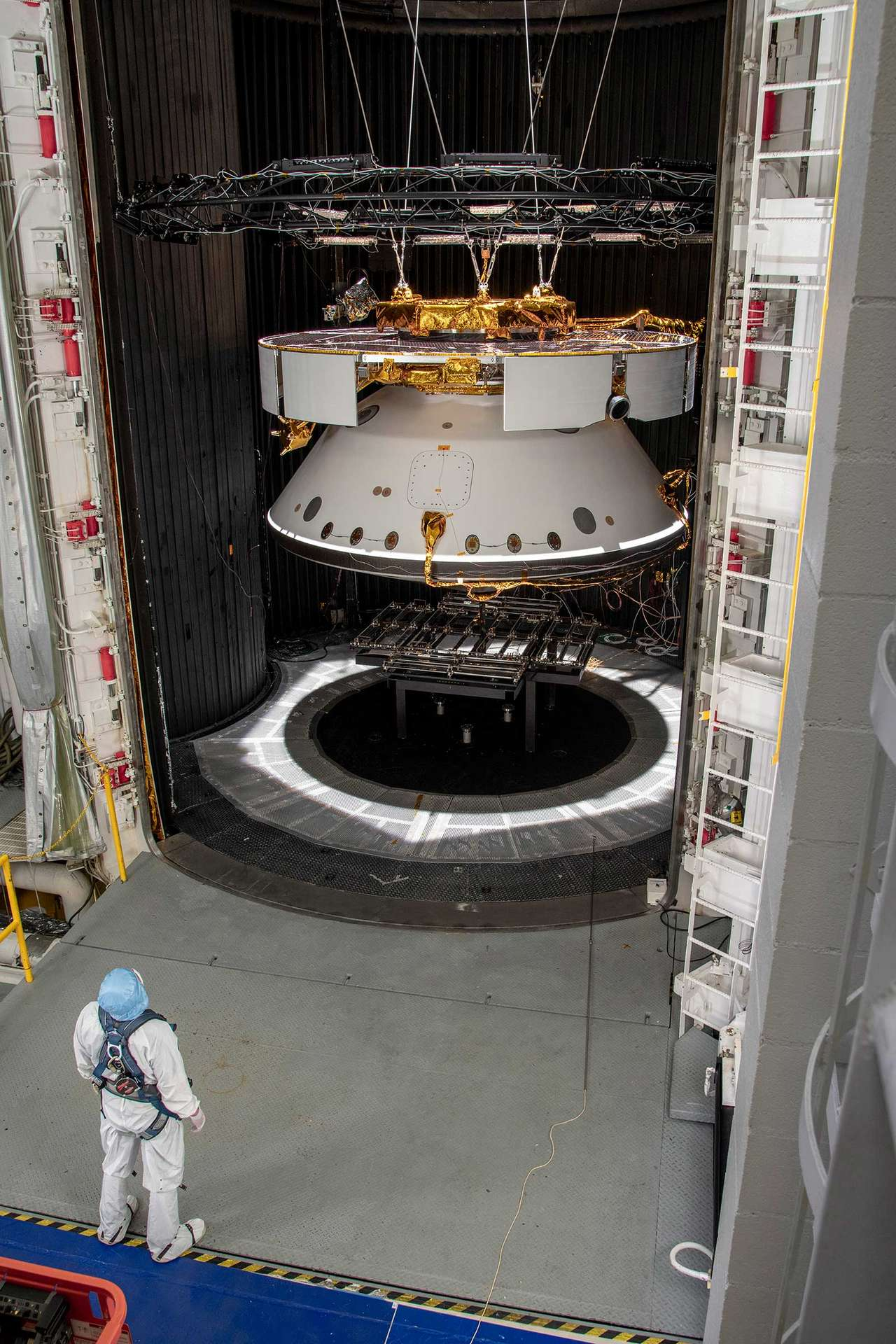 Un ingénieur du Jet Propulsion Laboratory (JPL) inspecte la sonde spatiale de la mission Mars 2020 qui patiente ici dans une chambre de simulation spatiale le 9 mai 2019, en attendant d'y être testée. © NASA JPL/CalTech.