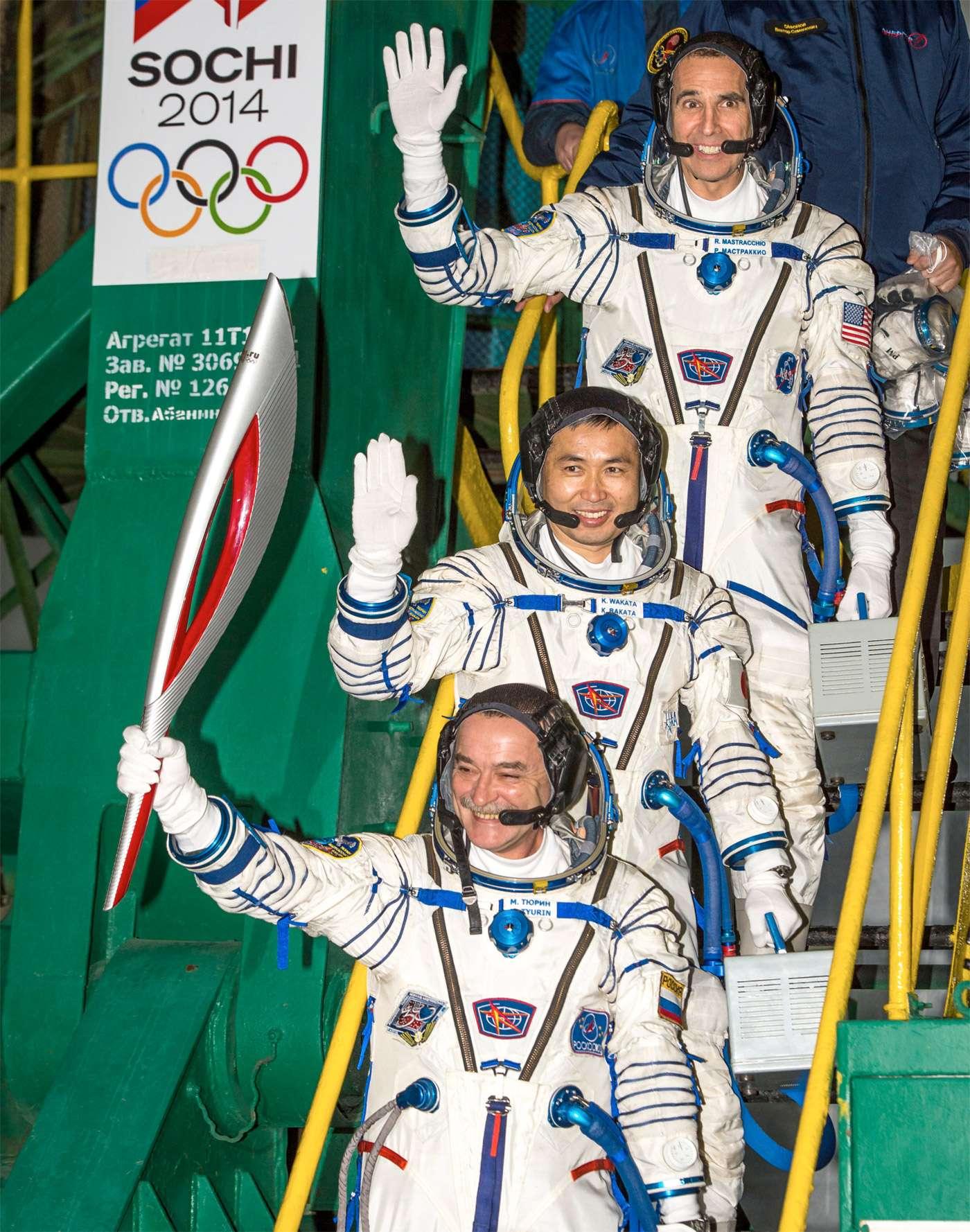 Les trois membres de l'Expédition 38 et la torche olympique, avant de prendre place à bord de la capsule Soyouz. Le périple de la torche prendra fin à l'ouverture des Jeux de Sotchi, début février 2014. © Bill Ingalls, Nasa
