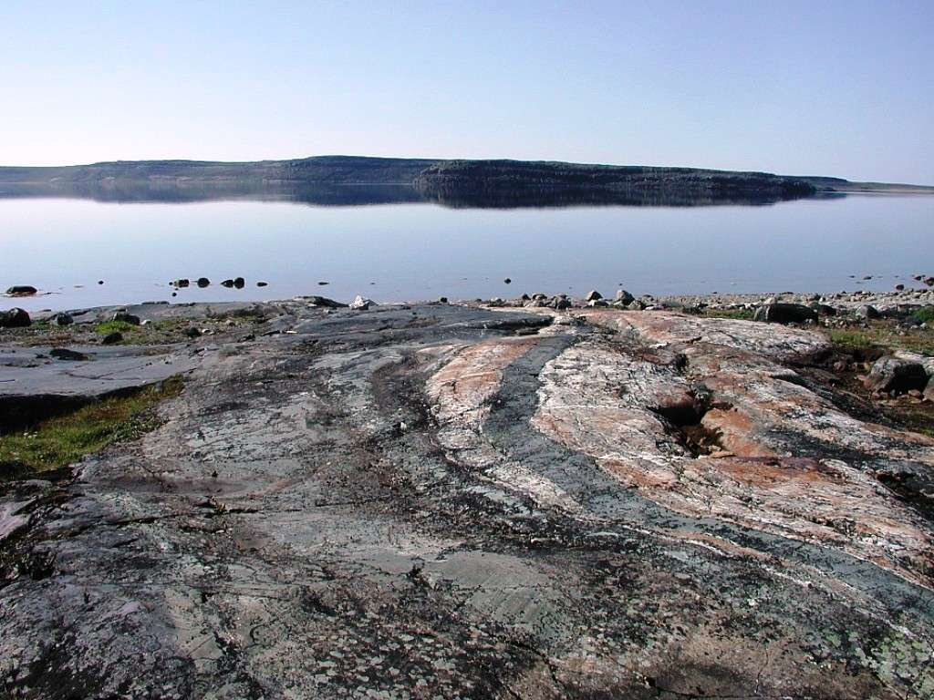 Une photographie d'un affleurement de roches métamorphiques à Porpoise Cove, de la ceinture supracrustale du Nuvvuagittuq (Canada). Certaines de ces roches ont un rapport Sm/Nd indiquant un âge de plus de 4,0 milliards d'années. Elles feraient donc partie, peut-être, des plus anciennes roches sur Terre. © Nasa Astrobiology Institute
