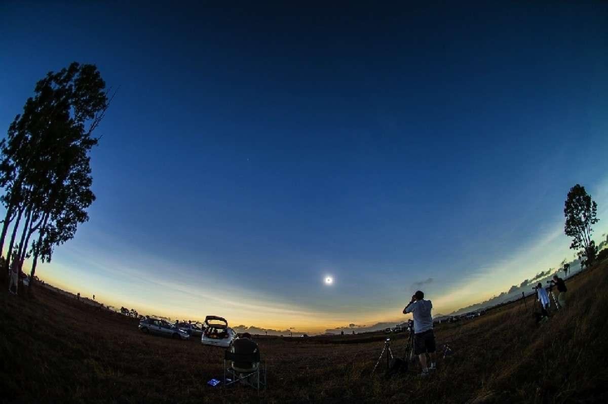 Phase totale de l'éclipse : le spectacle est grandiose, il fait de nouveau nuit 2 heures après le lever du soleil en Australie. Autour du masque lunaire se déploie la couronne solaire et l'horizon illuminé marque les limites du cône d'ombre. © Alan Dyer