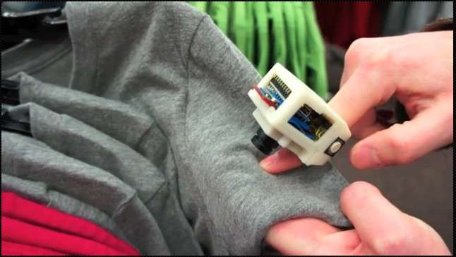 La bague EyeRing est ici pointée vers le T-shirt afin de détecter sa couleur. Pour cela, l'utilisateur presse le bouton latéral avec son pouce pour prendre une photo. Elle est transmise au smartphone (Android 2.2) par une connexion Bluetooth pour être analysée par l'application d'analyse d'image. Puis une application de reconnaissance va se charger de convertir la réponse sous forme vocale pour la transmettre via les écouteurs. © Suranga Nanayakkara/Roy Shilkrot/Patricia Maes/MIT Media Lab