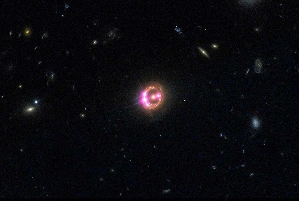 L'anneau d'Einstein, que l'on voit ici sur cette image composite réalisée à partir d'observations réalisées dans le visible avec Hubble et dans le domaine des rayons X avec Chandra, montre des images démultipliées du quasar RX J1131-1231. Il s'agit d'un effet de lentille gravitationnelle provoqué par une galaxie elliptique massive s'étant interposée entre ce quasar et nous. © Rayons X : Nasa, CXC, université du Michigan, R. C. Reis et al. ; optique : Nasa, STScI