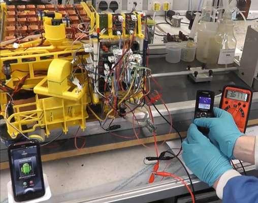 Le téléphone de droite a été rechargé par des piles à combustible microbiennes fonctionnant à l'urine (visibles en arrière-plan). Il appelle le portable situé en bas et à gauche de l'image. © Ieropoulos et al., 2013, Physical Chemistry Chemical Physics
