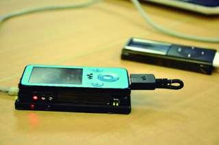 Le prototype de chargeur-transmetteur tel qu'il a été montré au Japon : un mobile repose sur un berceau. Il reçoit de l'électricité sans contact électrique, par induction magnétique, tandis qu'il échange des données par le même procédé. © Tech On