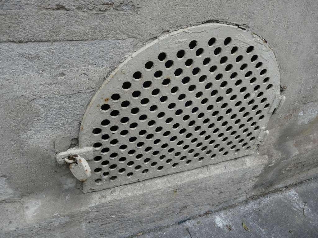 Un soupirail est presque toujours protégé par des barreaux ou, comme ici, par une grille. © Jean-Claude FORNEROD, CC BY-NC-ND 2.0, Flickr