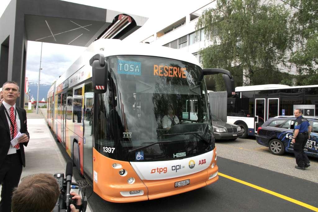 Le bus électrique Tosa à l'arrêt, à l'une de ses sous-stations de recharge flash. Le rail de connexion est visible en blanc, au-dessus du véhicule. © Tosa2013