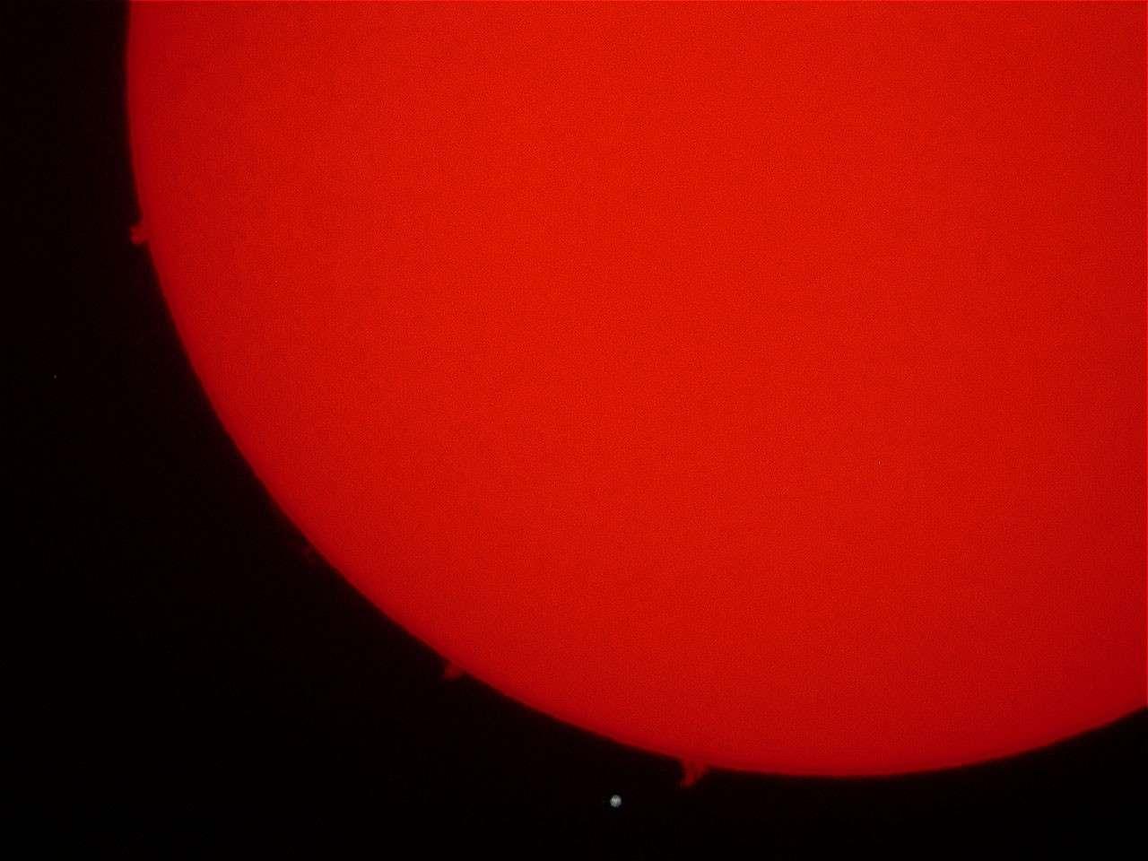 """Un morceau de la surface solaire et ses protubérances avec la Terre à l'échelle. Crédit """"Roule"""" du forum d'astronomie de Futura-Sciences"""