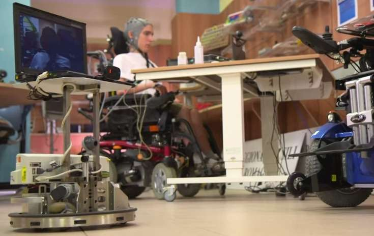 Le robot de téléprésence que l'on voit au premier plan à gauche est piloté par la personne handicapée munie d'un casque EEG. L'expérience a été menée par l'École polytechnique fédérale de Lausanne (Suisse) qui a développé une interface cerveau-machine grâce à laquelle des personnes valides ou paralysées ont pu commander à distance un robot muni d'un système de vidéoconférence. © EPFL, YouTube