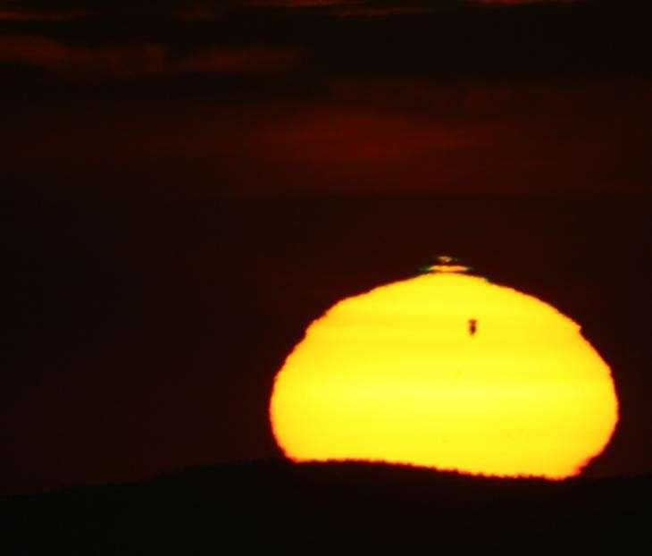 Une image qui fera date : le Soleil se lève, déformé par la diffraction atmosphérique qui torture Vénus et déclenche un fugace rayon vert. © Rico Hickmann