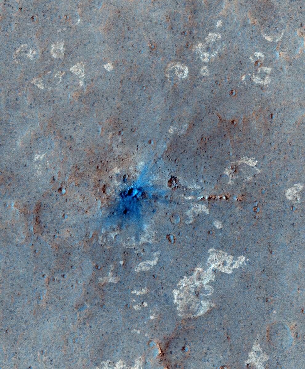 Sur cette image en fausses couleurs, on remarque très nettement les matériaux (en bleu) projetés autour d'un très jeune cratère martien de quelques mètres de diamètre creusé par la chute d'une petite météorite il y a moins de 7 ans. © Nasa, JPL, université d'Arizona