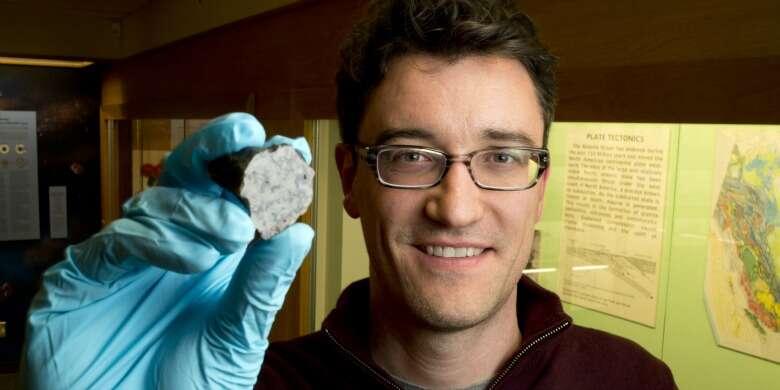 Chris Herd est le conservateur de la collection de météorites à l'Université de l'Alberta. Outre la minéralogie et la pétrologie, Chris Herd tient au premier rang de son carnet de recherche la planétologie comparative qui a pour but l'évaluation comparative d'échantillons de la terre avec ceux de Mars, de la Lune et d'une variété d'astéroïdes. On le voit ici tenir un fragment de la météorite de Tissint. © University of Alberta-John Ulan