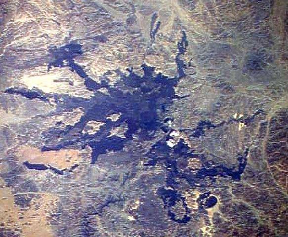 Le site de Harrat Lunayyir, à l'est de la mer Rouge, photographié par un membre d'équipage de la Station spatiale en 1988. On remarque, en bleuté, cet épanchement de lave, depuis longtemps solidifié. En sous-sol, des fissures ont laissé remonter en 2009 des coulées de magma qui ont fait trembler la terre mais ne sont pas parvenues jusqu'à la surface. © NASA Space Shuttle image STS26-41-61