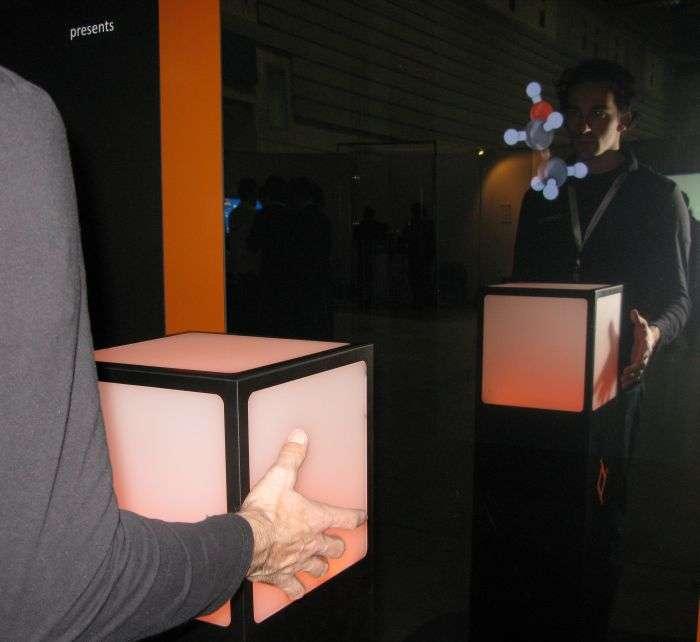 Debout devant le Cubtile, l'homme manipule à l'aide de ses deux mains, en effleurant les surfaces tactiles, l'objet apparaissant devant lui sur le miroir-écran. © Nikkei Electronics