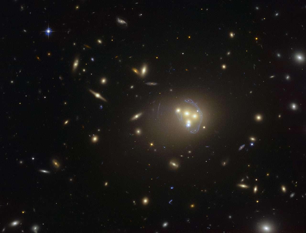 Cette image acquise par le télescope spatial Hubble du consortium Nasa-Esa montre le riche amas galactique Abell 3827. Les étranges structures de couleur bleue qui entourent les galaxies centrales constituent des vues agrandies, par effet de lentille gravitationnelle, d'une galaxie plus lointaine située derrière l'amas. Des observations de la fusion des quatre galaxies centrales ont démontré que la matière noire entourant l'une des galaxies ne suit pas le mouvement de la galaxie elle-même. Ce résultat permet d'envisager l'existence d'interactions matière noire – matière noire de nature inconnue. © ESO