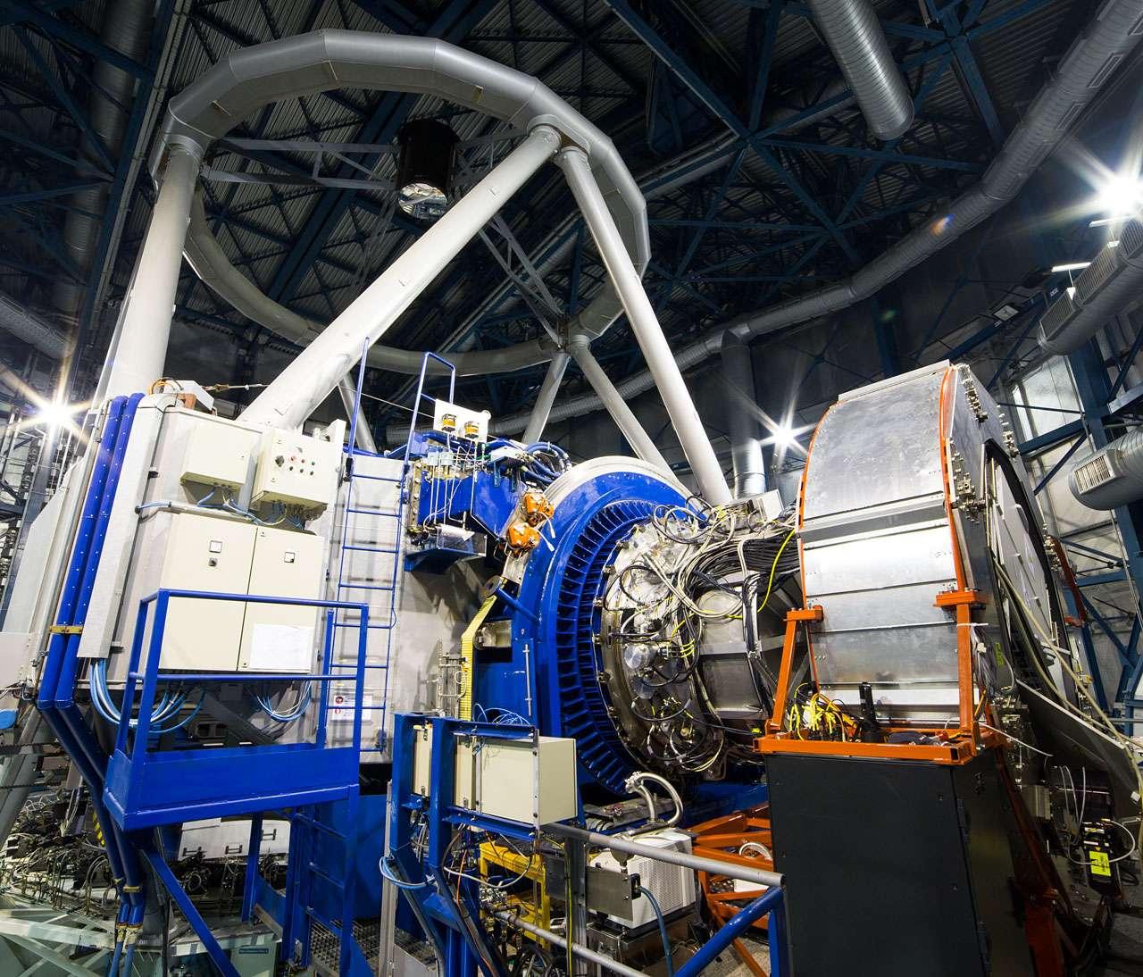 L'instrument KMos installé au foyer du Very Large Telescope (VLT) de l'ESO à l'observatoire de Paranal au Chili. Sur cette image, KMos est la structure argentée au centre, entourée par l'anneau bleu qui le connecte au télescope unitaire 1 du VLT, qui apparaît sur la gauche. Sur la droite, le grand cylindre argenté supporte l'ensemble de l'électronique de KMos et lui permet de tourner quand le télescope se déplace sur le ciel. © ESO, G. Lombardi