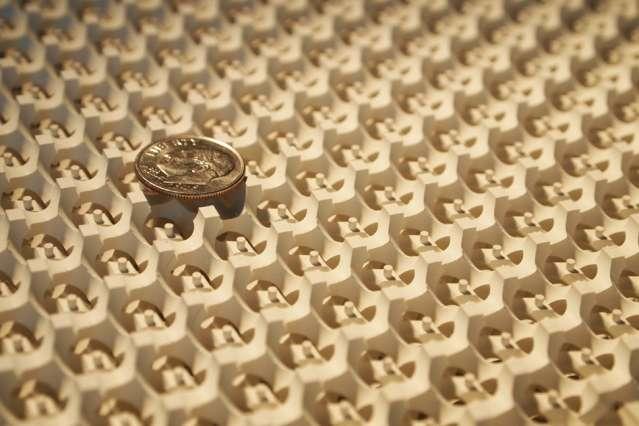 Pour observer le fermion de Weyl, les chercheurs du MIT se sont appuyés sur un cristal structuré en gyroïde, ici surmonté d'une pièce de monnaie. © Ling Lu et Qinghui Yan
