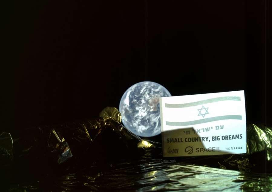 Le message « Un petit pays, de grands rêves » et le drapeau d'Israël visibles sur ce selfie pris dans l'espace par la première sonde lunaire israélienne, à une distance de 37.600 km de la Terre en arrière-plan. La photo a été diffusée le 5 mars 2019 par SpaceIL et Israel Aerospace Industries (IAI). © SpaceIL, IAI, AFP