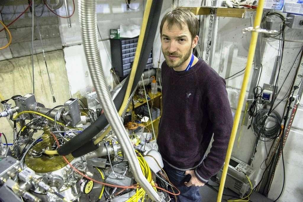 Stephan Ettenauer, un étudiant postdoctoral travaillant sur l'expérience Atrap, devant le dispositif dit de « piège de Penning », qui sert à piéger les antiprotons. © Anna Pantelia, Cern