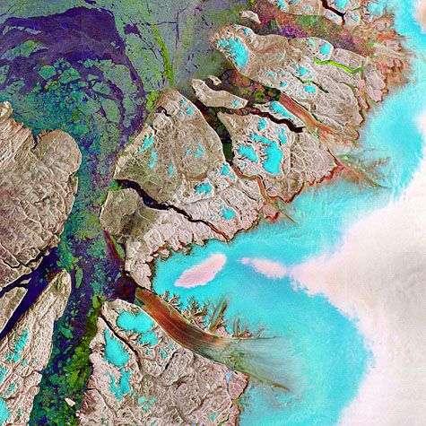 Les fausses couleurs indiquent la nature du sol. Le bleu et le blanc correspondent à la couverture de glace du Groenland. De teinte rougeâtre sur cette image, le glacier Petermann flotte sur la mer et s'écoule dans le détroit de Nares, ici en vert en en bleu-violet. Crédit : Esa