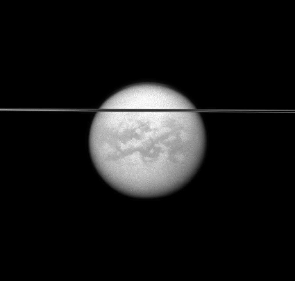 Les anneaux de Saturne vus par la tranche se découpent devant le satellite Titan. © Nasa/JPL-Caltech/Space Science Institute