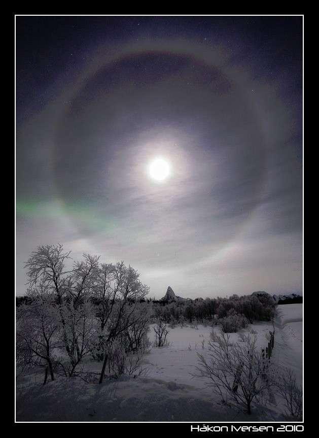 Un halo lunaire accompagné d'une légère aurore boréale verte. © Hakon Iversen