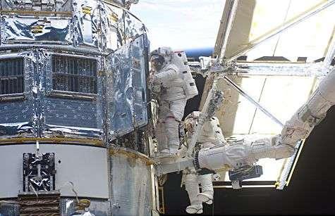Dernière mission de maintenance de Hubble, le 6 mars 2002 (STS109). Les astronautes John M. Grunsfeld et Richard M. Linneh procèdent au remplacement d'un contrôleur d'alimentation en énergie électrique. Crédit Nasa