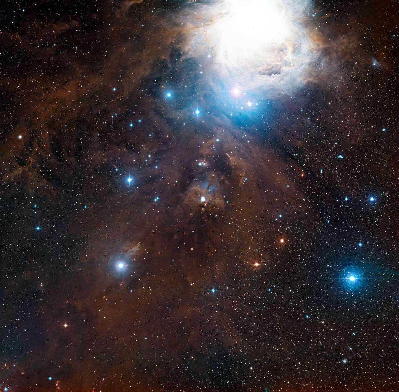 Cette image à grand champ montre la région autour de la nébuleuse par réflexion NGC 1999 dans la fameuse constellation d'Orion en lumière visible. NGC 1999 se trouve au centre de l'image. La grande structure brillante en haut de l'image est la nébuleuse bien connue d'Orion (Messier 42). Cette vue a été créée à partir de clichés du Digitized Sky Survey 2. © ESO, Digitized Sky Survey 2, Davide De Martin