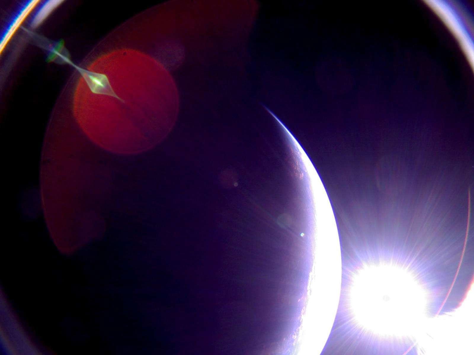 Image de la Terre et du Soleil (en bas à droite) peu avant que celui-ci ne disparaisse à l'horizon, prise par la voile solaire LightSail-2 le 6 juillet 2019. Sur cette image non retouchée, les artefacts proviennent de la diffusion de la lumière à l'intérieur de l'objectif de la caméra. Il s'agit par ailleurs d'un objectif fisheye avec un vaste champ de vision (180°), mais responsable des arcs brillants aux coins de l'image et source de distorsion. © The Planetary Society