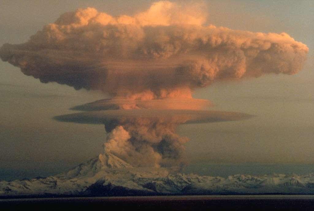 Photographie de l'éruption du mont Redoubt, en Alaska, le 21 avril 1990. La nuée ardente se compose de la coulée pyroclastique observée à droite du volcan, d'où s'est élevé le nuage en forme de champignon visible au centre de l'image. © R. Clucas, USGS, DP