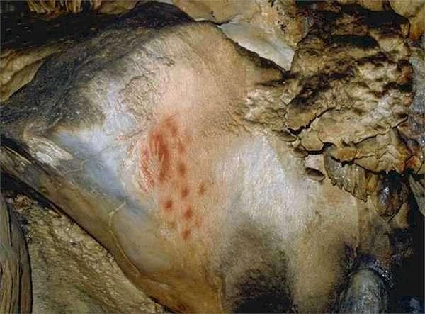 Dans la grotte du Pech Merle, une main en négatif côtoie treize points. Que voulait nous dire l'artiste ? On l'ignore, mais Dean Snow pense que c'était une femme. © Centre de préhistoire du Pech Merle