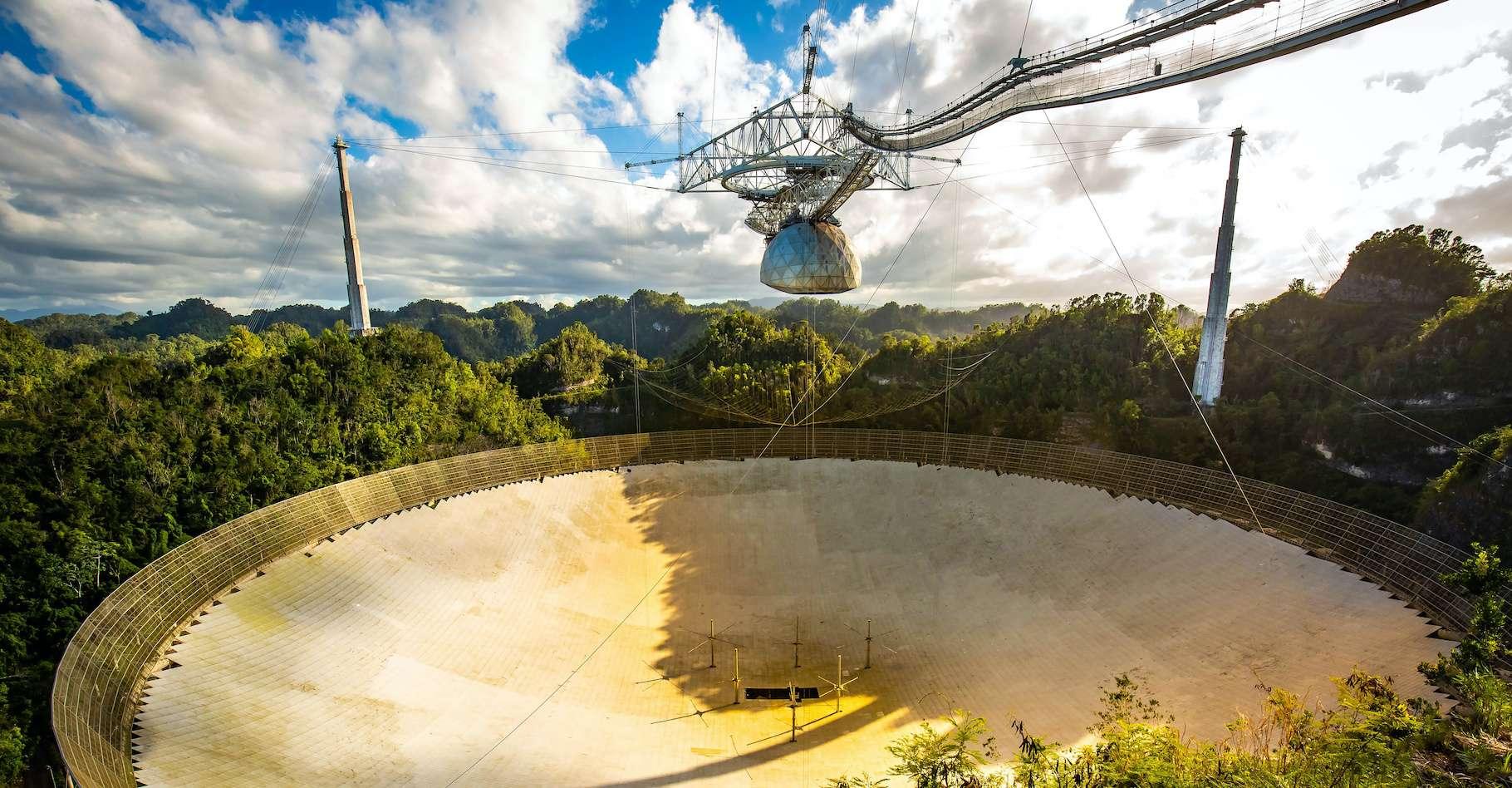 Le radiotélescope d'Arecibo a longtemps été le plus grand radiotélescope simple jamais construit. En ce début de semaine, il a été gravement endommagé par un incident technique. © PhotoSpirit, Adobe Stock