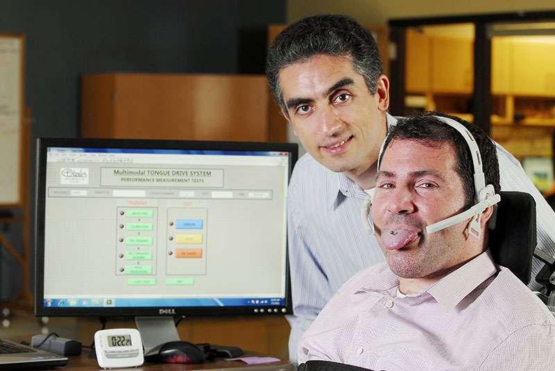 Maysam Ghovanloo, le directeur de cette étude, se tient derrière Jason DiSanto, un patient tétraplégique et un des premiers à tester le Tongue Directional System (TDS) qui permet de piloter un fauteuil roulant avec la langue. Sur l'image, on peut apercevoir l'aimant accroché à sa langue. © Maysam Ghovanloo, Georgia Tech