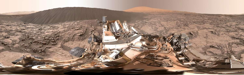 Panorama couvrant 360° composé avec les images acquises par Curiosity le 18 décembre 2015 (Sol 1.197). La « dune de Namib » est à environ 7 m du rover que l'on voit au premier plan, partiellement couvert de poussière rouge. L'est est au centre de l'image, tandis que les bords qui se rejoignent indiquent l'ouest. Derrière, à droite de la dune de sable noir, on reconnait le mont Sharp. Téléchargez l'image en haute résolution (8,3 mb) ici. © Nasa, JPL-Caltech, MSSS