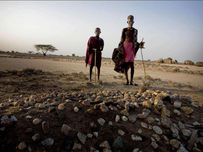 En 2011, l'Afrique de l'Est a connu une grande sécheresse. Beaucoup d'autochtones ont perdu la vie. Sur la photo, Eyanai et son grand-père Napathar se tiennent devant la tombe de la femme de Napathar, qui est décédée de malnutrition durant la sécheresse. © Kate Holt