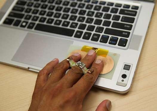 Système de communication par énergie corporelle mis au point par deux étudiants stagiaires d'Intel, qui se compose de deux capteurs tactiles reliés chacun à un PC portable et d'une bague qui collecte le signal électromagnétique transitant par le corps humain. Durant ses essais, l'équipe est parvenue à faire le copier-coller d'un fichier de quelques octets contenant une émoticône. © Intel
