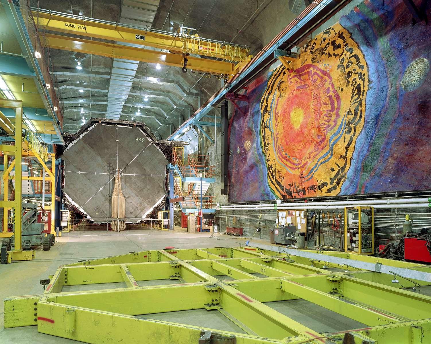 Au fond à gauche, le détecteur Minos dans sa caverne de la mine Soudan. A droite, une fresque rassemble des dessins des physiciens Enrico Fermi et Woflgang Pauli. Crédit : Fermilab