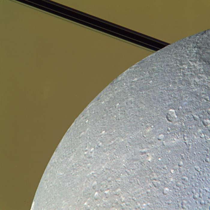 Image composite colorisée montrant la surface de Dioné alors que le satellite est en train de passer devant Saturne et ses anneaux. © Nasa/JPL/SSI/J. Major