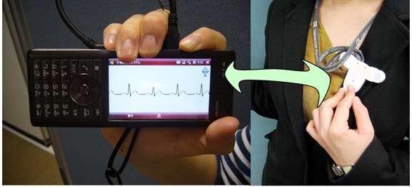 L'électrocardiographe se porte attaché à un collier passé autour du cou. Il surveille en permanence un certain nombre de paramètres physiologiques, le rythme cardiaque, la température et la position du corps par rapport à l'horizontale. Les données sont transmises à un mobile équipé d'un adaptateur. © NICT / Tech-On