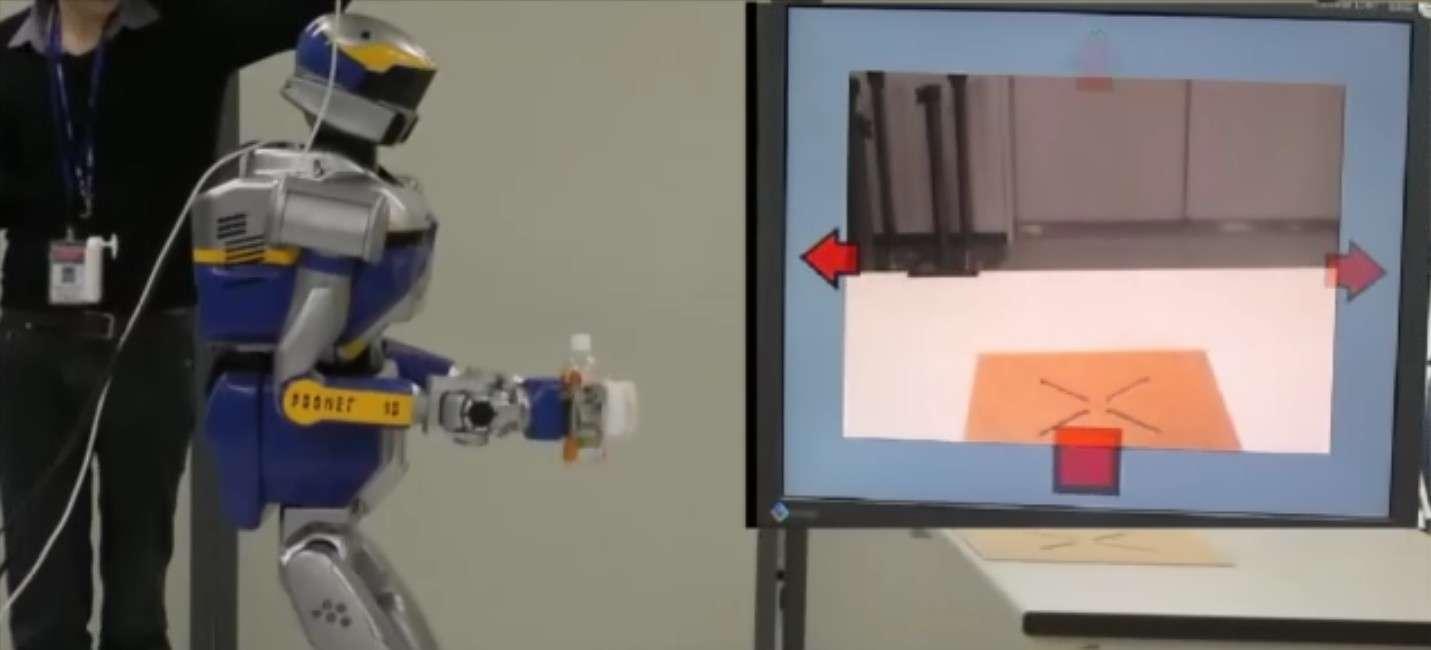 Les chercheurs français et japonais du Joint Robotics Laboratory sont parvenus à développer un système de contrôle par la pensée multitâche grâce auquel il est possible de réaliser plusieurs actions. Ici, le robot a saisi une bouteille et il est ensuite guidé vers une table où il ira la déposer, le tout entièrement piloté à partir des pensées émises par l'opérateur humain équipé d'un casque EEG. © CNRS-AIST JRL
