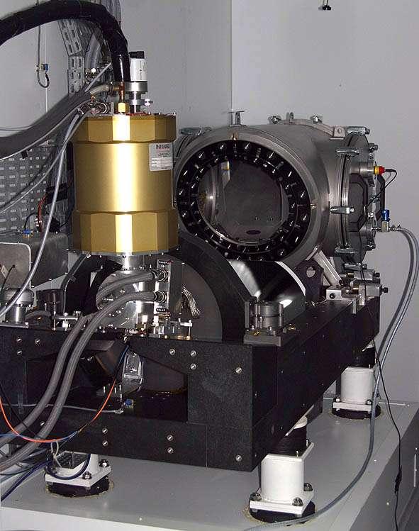Le spectrographe Sophie, sur ses quatre pieds anti-vibrations. Il reçoit la lumière du télescope par quatre fibres optiques (grises, en haut à gauche). La lumière est envoyée à travers le hublot (une lame de Schmidt, au centre). © OAMP