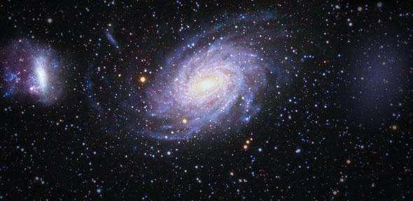 Des astronomes ont découvert une énorme galaxie naine satellite de la Voie lactée (au centre de l'image), baptisée Antlia 2 (représentée à droite de l'image sous forme d'un nuage très diffus). Elle est très étrange car elle est immense, presque aussi grosse que le Grand Nuage de Magellan (à gauche), mais elle est des milliers de fois moins lumineuse. © V. Belokurov based on the images by Marcus and Gail Davies and Robert Gendler