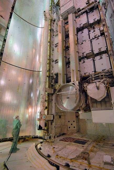 Une vue impressionnante des panneaux solaires repliés dans la soute de Discovery à l'intérieur du bâtiment d'intégration, quelques jours avant le lancement. Le disque argenté visible à mi-hauteur est le joint rotatif sur lequel sont fixés les deux panneaux, dont les boîtiers qui les renferment sont visibles plus haut. Crédit Nasa