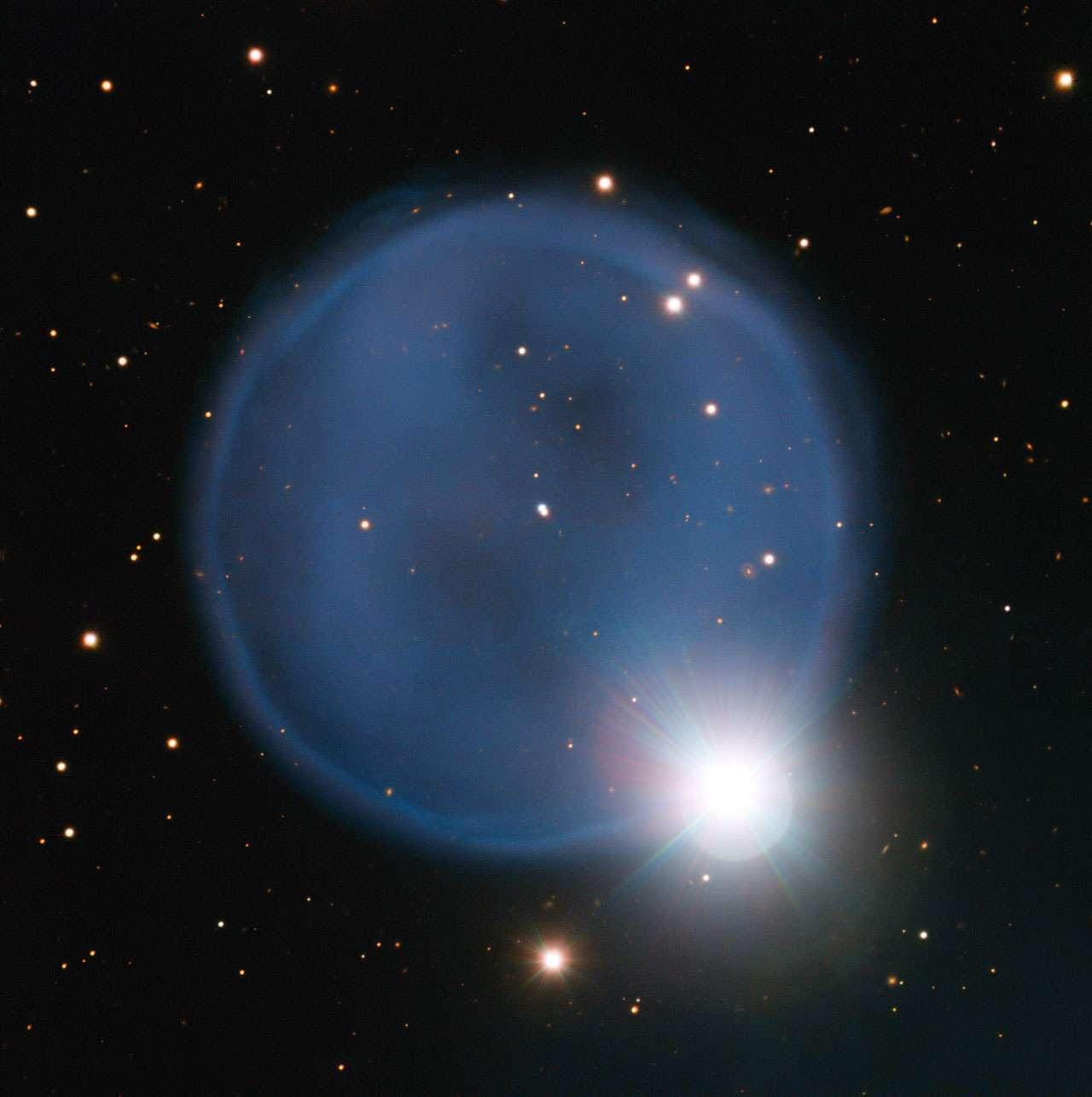 La nébuleuse planétaire Abell 33 observée par le Très Grand Télescope (VLT) de l'ESO. Elle présente une forme sphérique presque parfaite, ce qui est rare, et laisse voir, au centre, l'étoile mourante qui a éjecté sa couronne. Une autre étoile, fortuitement alignée avec la Terre, donne à la nébuleuse l'aspect d'une bague sertie d'un diamant. © ESO