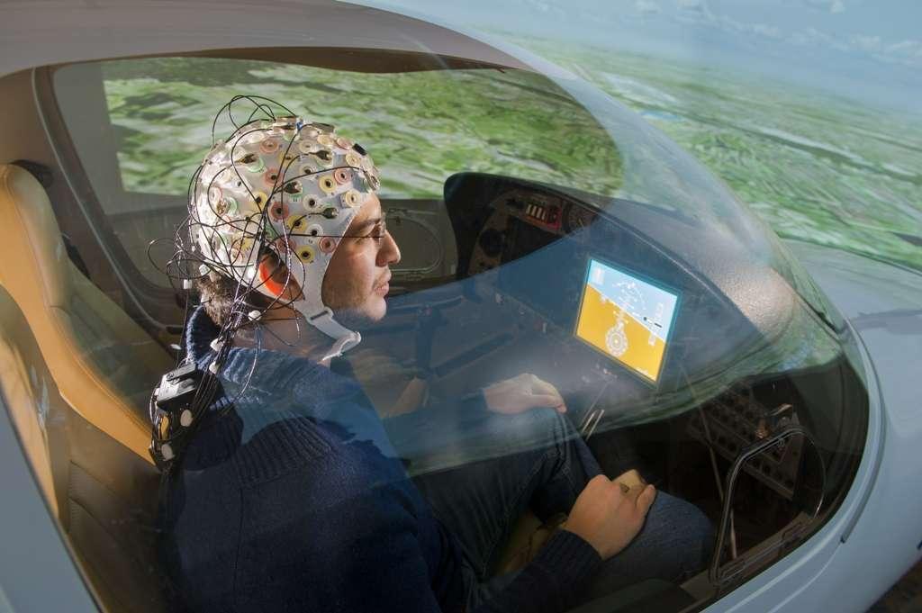 Les essais de pilotage par la pensée d'un avion n'ont jusqu'à présent été réalisés qu'avec un simulateur de vol. Ici, un cobaye porte la coiffe enregistrant les signaux de son cerveau lors d'un test conduit à l'institut des systèmes dynamiques de vol de la Technische Universität München (TUM) en Allemagne. © A. Heddergott/TU München