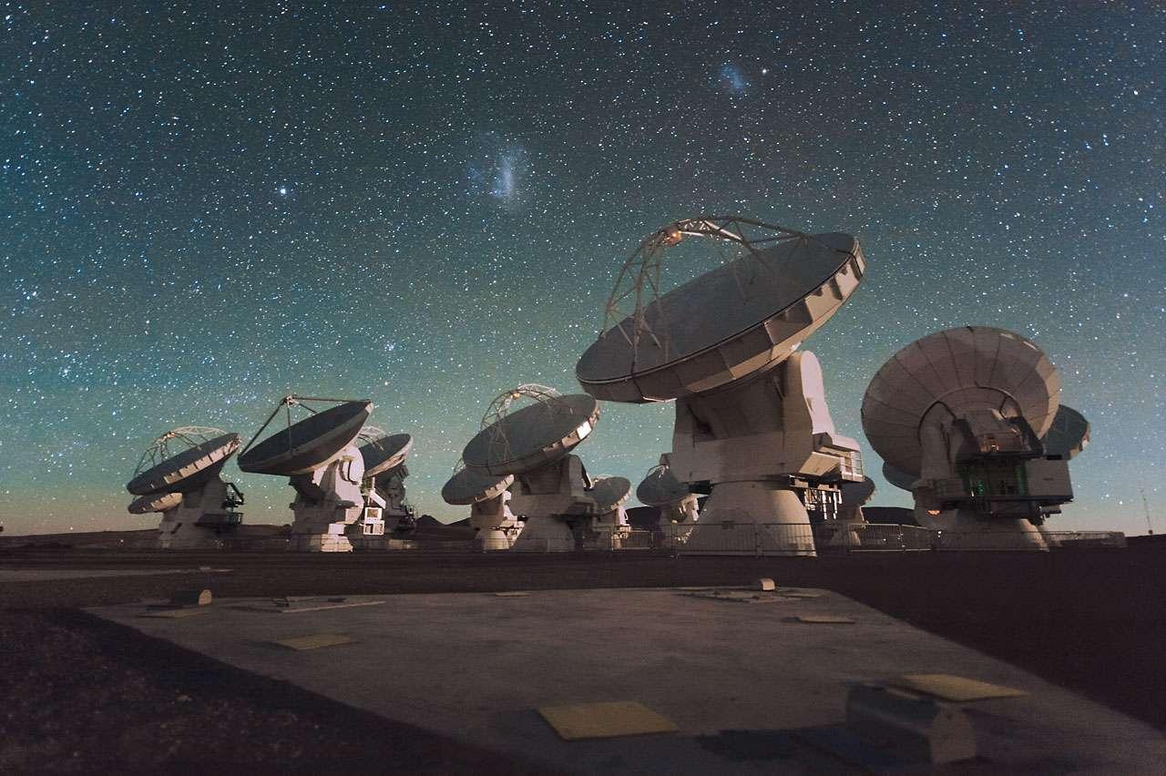 Les deux nuages de Magellan visibles au-dessus d'une partie du Vaste Réseau (Sub-) Millimétrique de l'Atacama, Alma. « À l'avenir, Alma produira des images de la structure fine des galaxies primordiales et retracera le détail de la formation des toutes premières galaxies » explique Roberto Maiolino qui a contribué à cette étude qui a permis de mieux cerner des galaxies très jeunes et lointaines. © Eso, C. Malin
