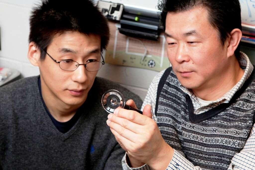 De gauche à droite, Lei Li et Allen Yi inspectant la lentille qu'ils viennent d'inventer. © Kevin Fitzsimons, Ohio State University